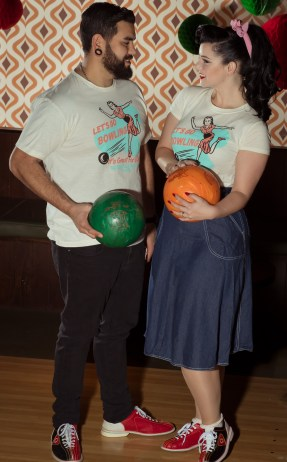 Couple in vintage style bowling t shirts holding bowling balls