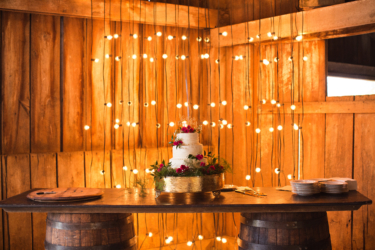 Kentucky summer wedding- rustic elegant barn wedding reception with three tiered wedding cake, bourbon barrel table and lights