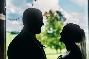 Silhouette photo of bride and groom with farm backdrop