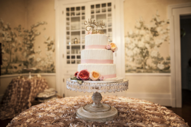 Ivory three-tiered cake on table with textured blush linen