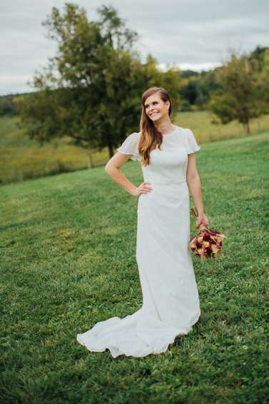 Bride dressed in conservative gown with farm backdrop