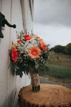 Country rustic bridal bouquet of baby's breath, coral roses and coral gerber daisies with burlap wrap