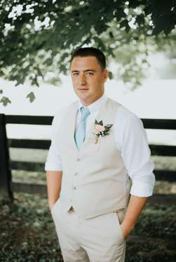 Southern charm groom dressed in light khaki with light blue tie and gerber daisy boutonniere