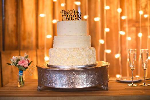 Ivory three-tier textured wedding cake with laser cut cake topper on sliver cake stand