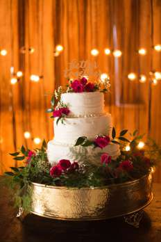 Three-tier ivory wedding cake with pink spray roses and greenery on a gold cake stand