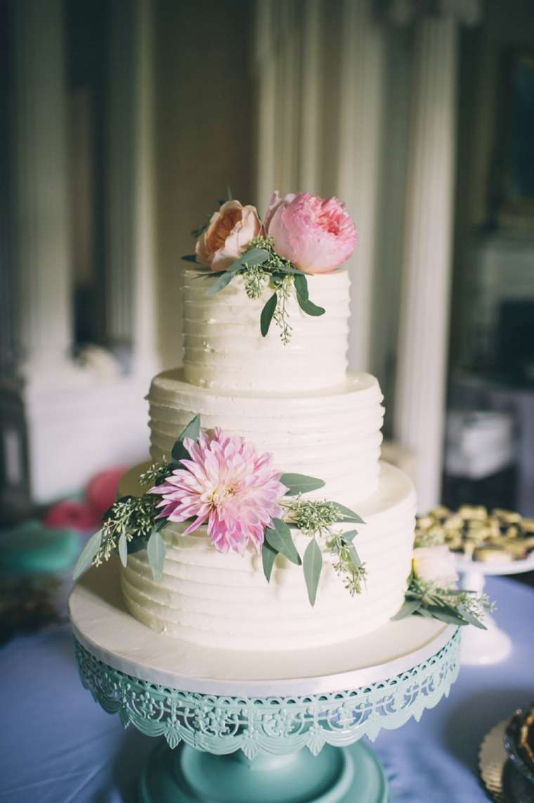 Textured three-tier ivory wedding cake with soft pink flowers