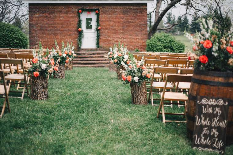 Wedding ceremony aisle with wood stumps and floral arrangements