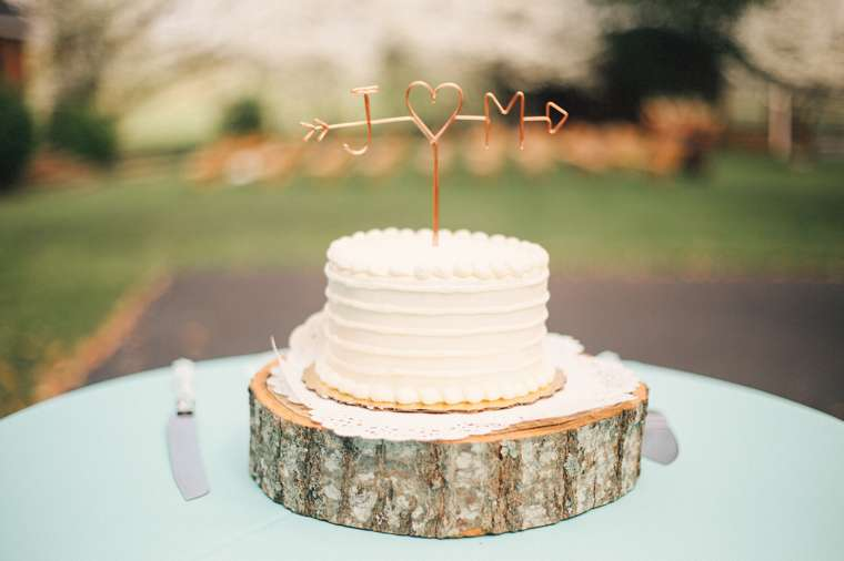 Single tier ivory wedding cake on wood slab with copper wire cake topper
