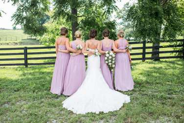 View of back of bridal party dressed in light purple, bride with long train