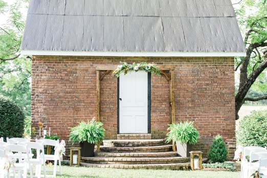Outdoor wedding backdrop with brick cottage, arch, greenery and candles