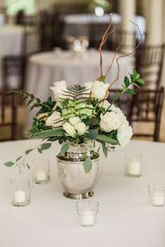 Ivory florals and greenery centerpiece in silver pitcher