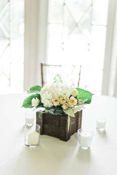 Ivory and blush flowers in wooden box for wedding reception centerpiece