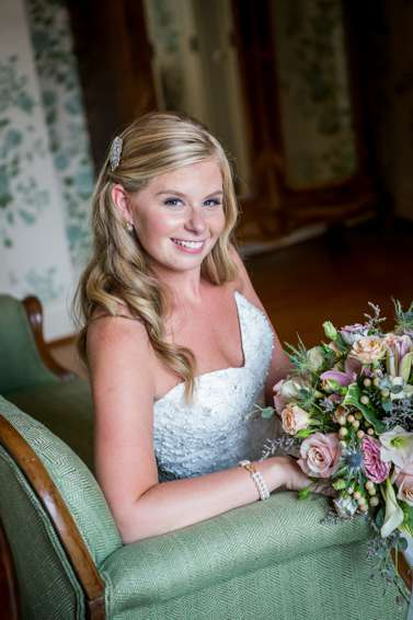 Bride with sweetheart cut neck line, loose curls and vibrant bouquet at Warrenwood Manor
