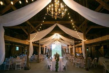 Warrenwood Manor barn with ivory drapery, chandeliers and string lights