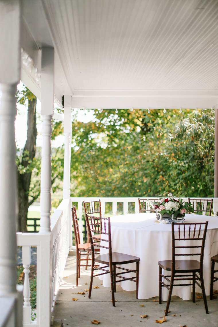 Outdoor reception setup with white linens along with bungundy, dusty pink and white flowers