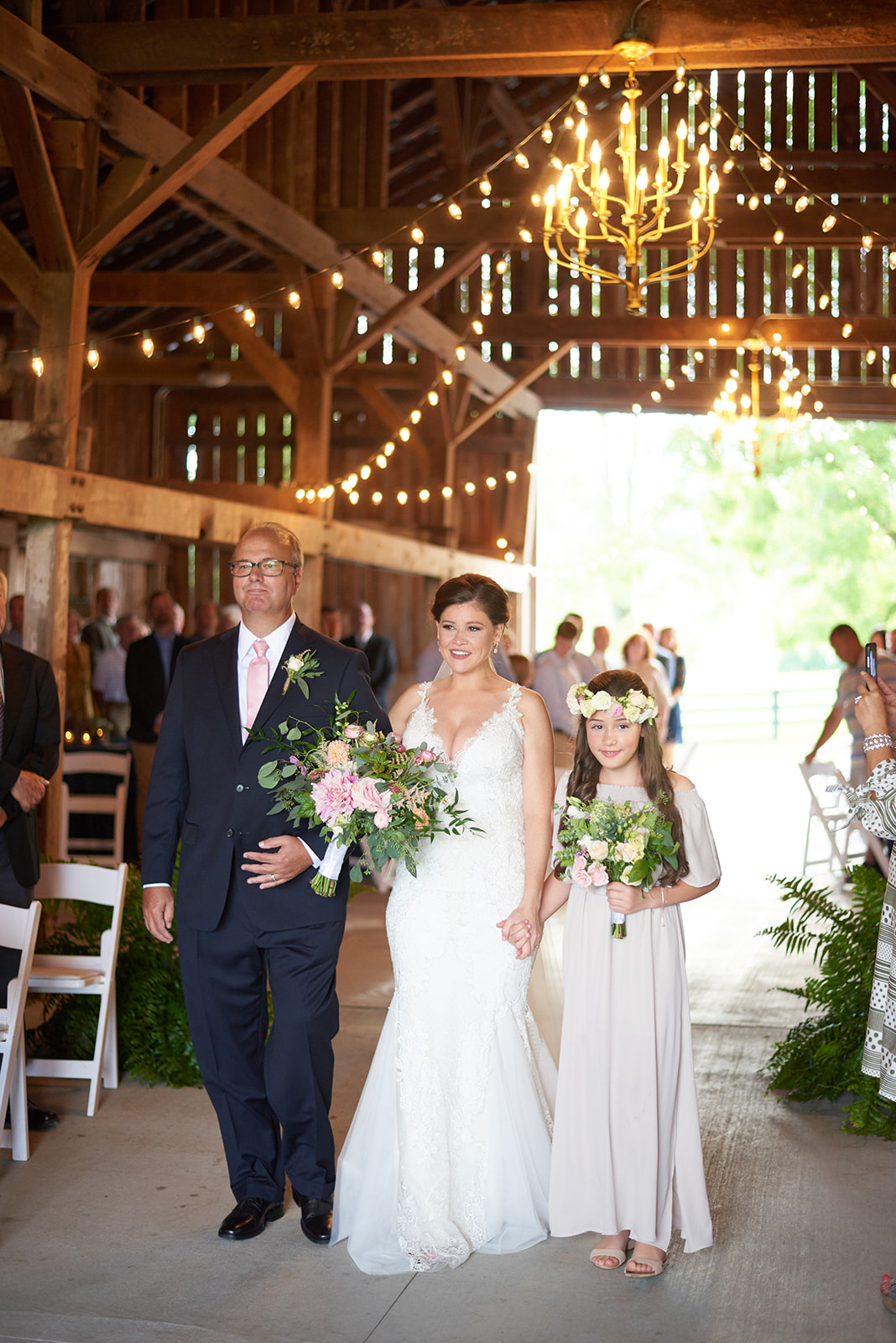 Bride being escorted into ceremony by father & daughter
