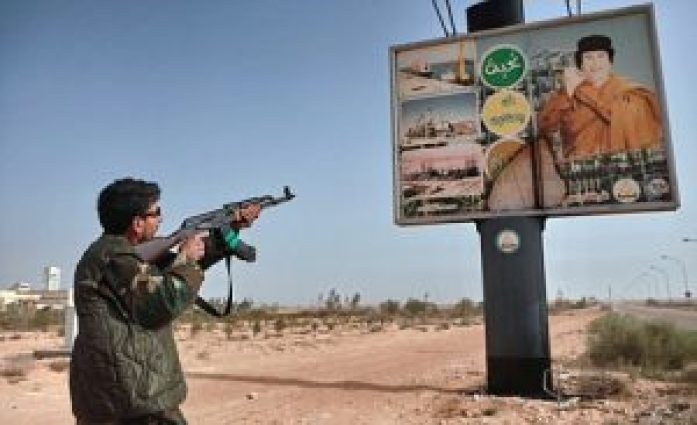 An armed supporter of the Libyan opposition shoots a machine gun at a poster with the image of Muhammar Gaddafi in the captured rebel town of Ras-Lanuf in the east of the country.