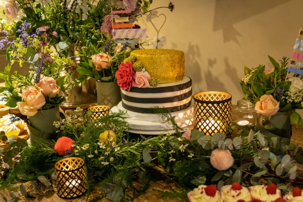 Two tiered birthday cake: gold tier and stripey black and white tier. Surrounded by tealights and flowers