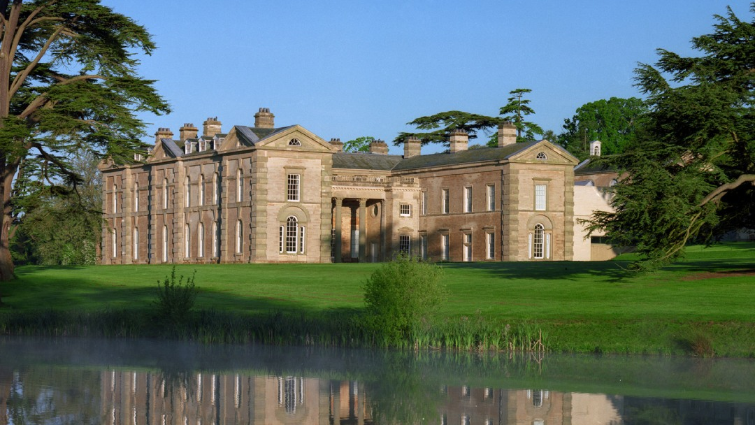 Grand stately home surrounded by trees, lake and grounds
