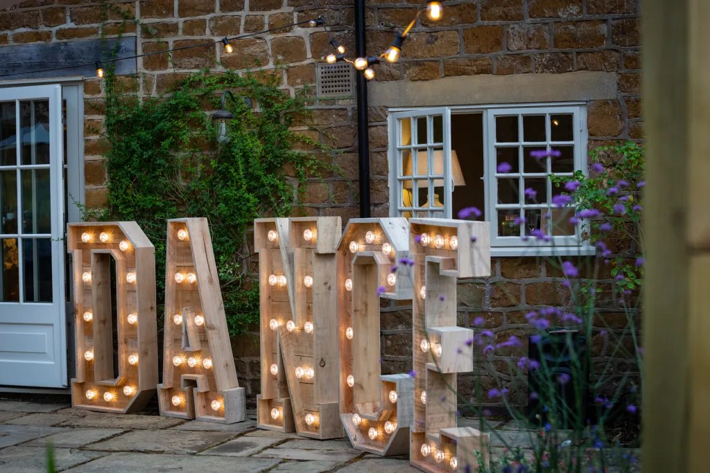 Festoon lights and large lit up DANCE letters on patio to create dance space for rustic-chic party