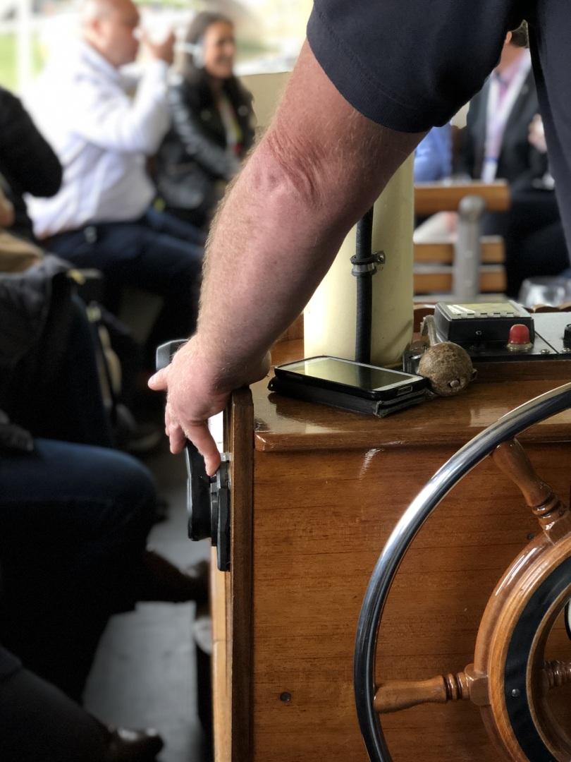 Man's arm steering Edwardian boat's steering wheel
