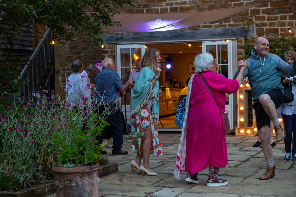 Guests dancing enthusiastically on outdoor patio at rustic-chic party