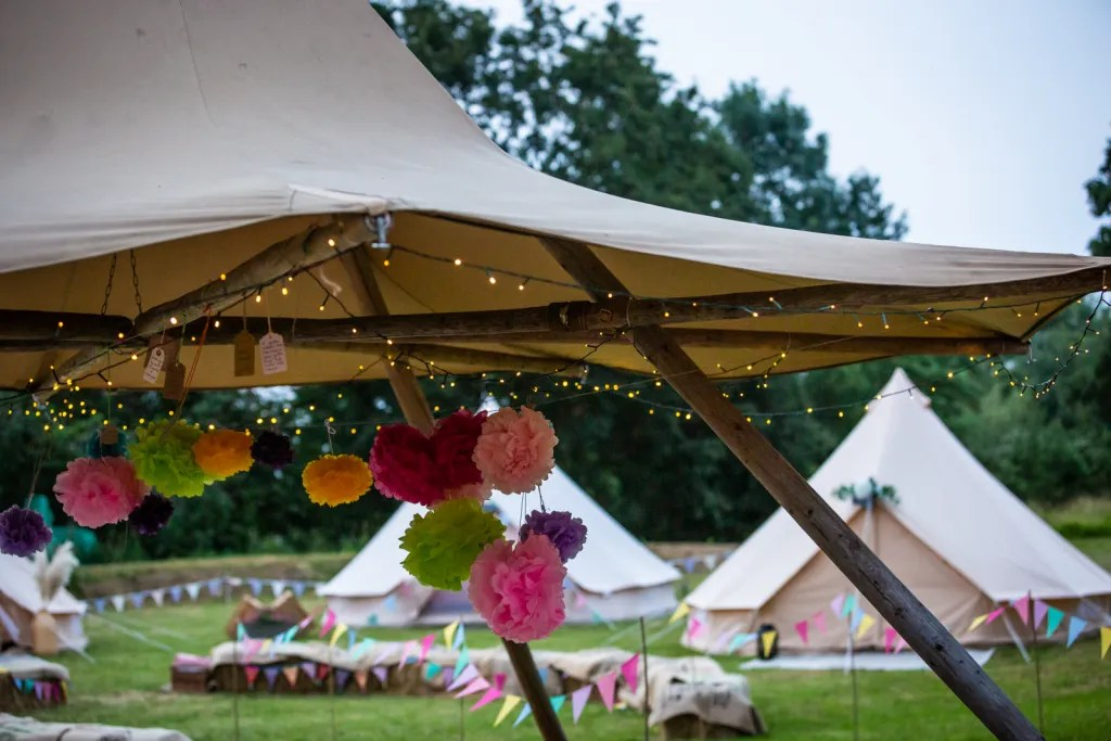 Tip with fairy lights and paper pompoms with glamping bell tents in background for rustic-chic party