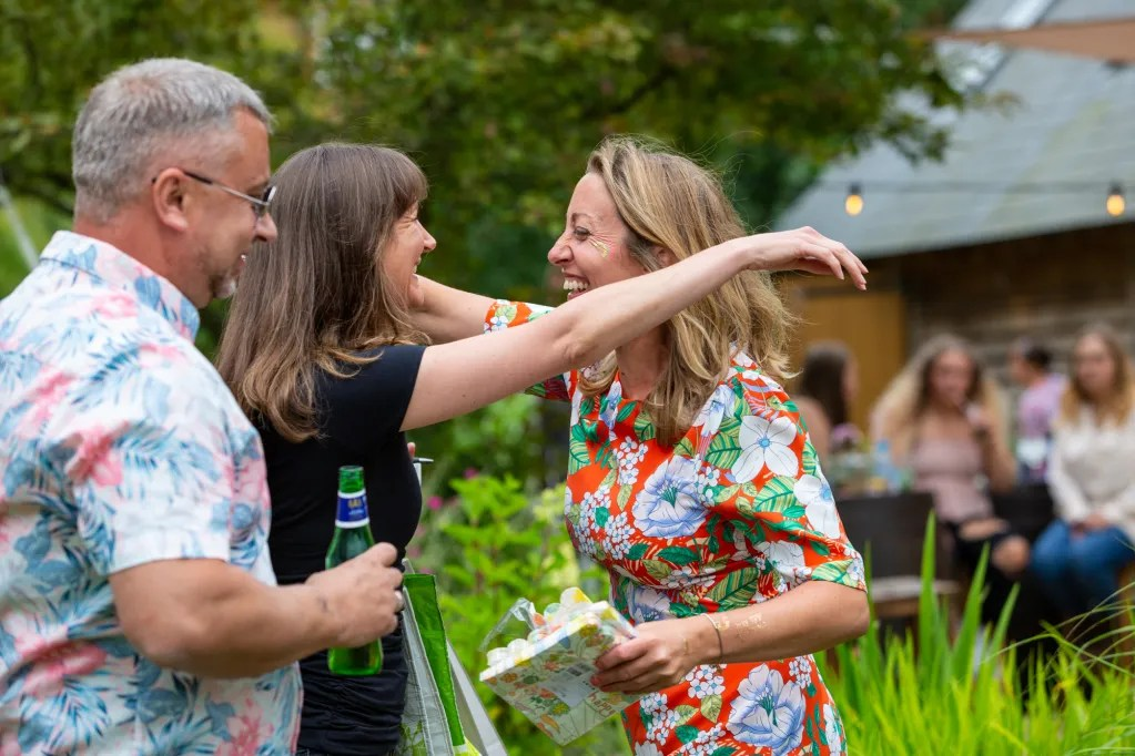 Birthday girl holiding gift, smiling and hugging guest at rustic-chic party