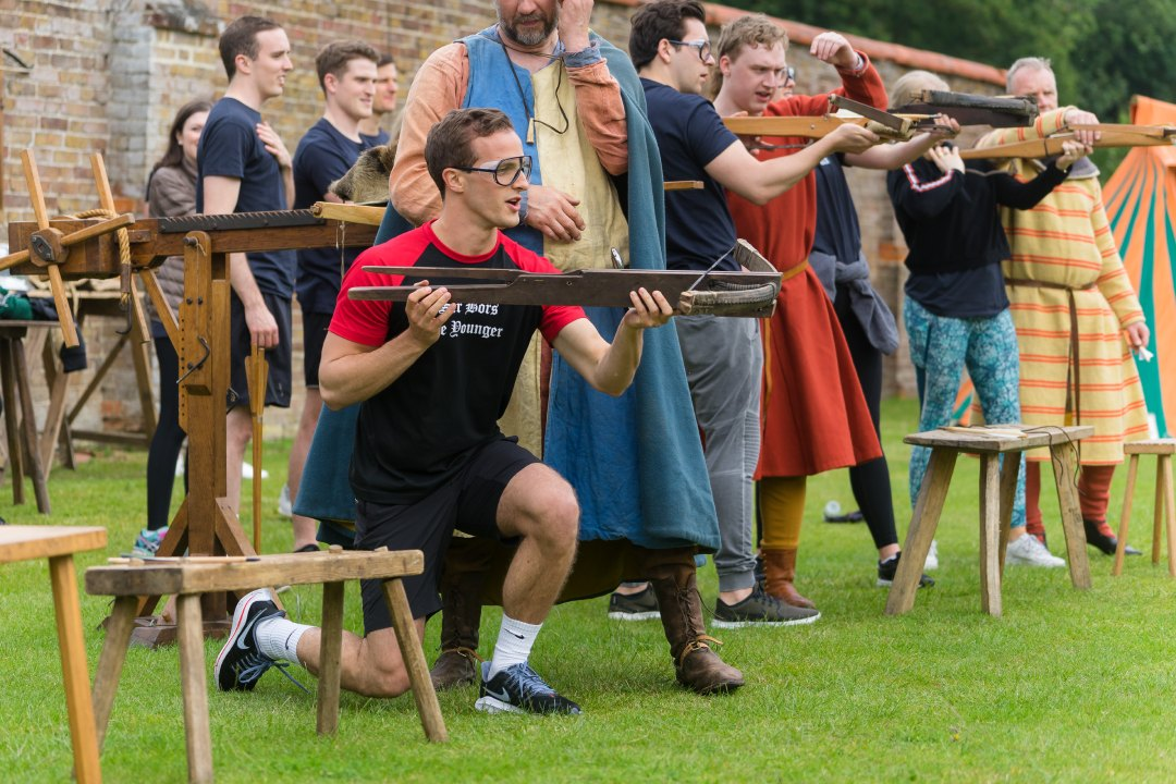 Man getting instruction in medieval cross bow team activity