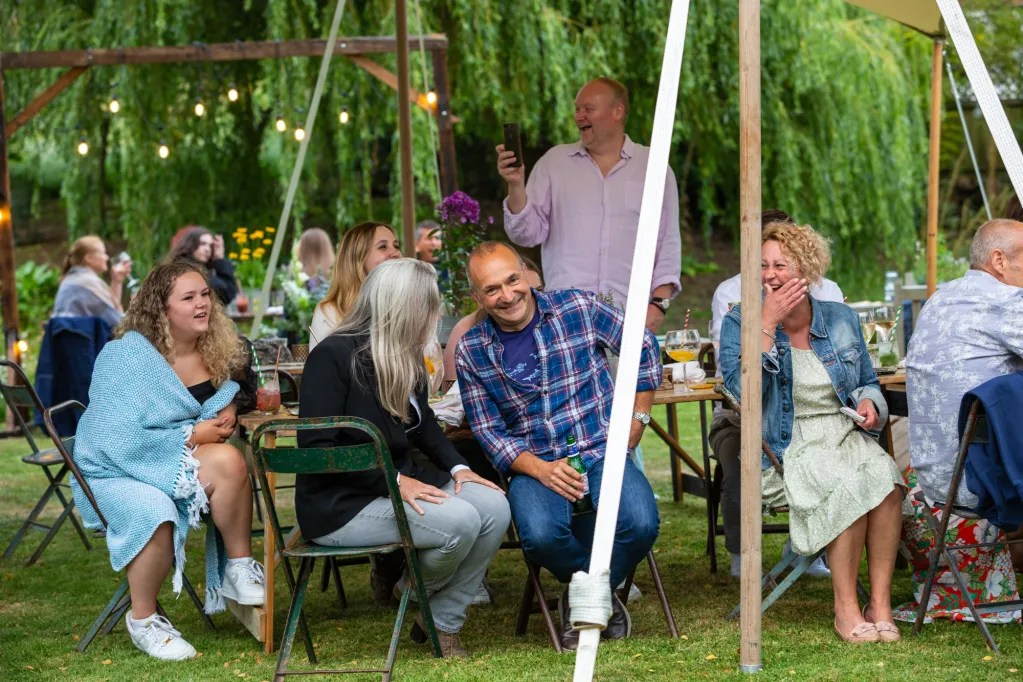 Guests lauging under canopy at garden party