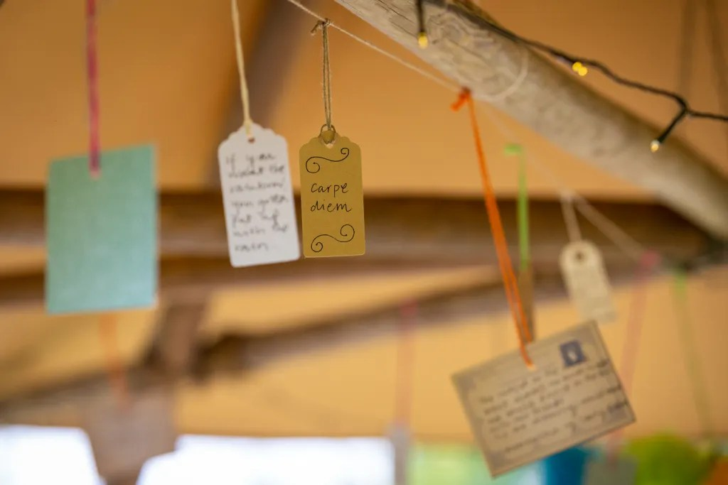 """Handwritten quote bunting hanging from tipi with fairy lights including """"Carpe diem"""""""