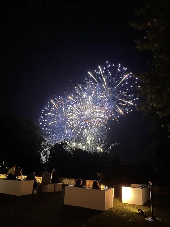 Guests watching fireworks in night sky, sat on ambiently lit outdoor sofas during VIP hospitality
