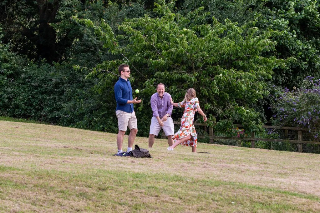People laughing while playing rounders