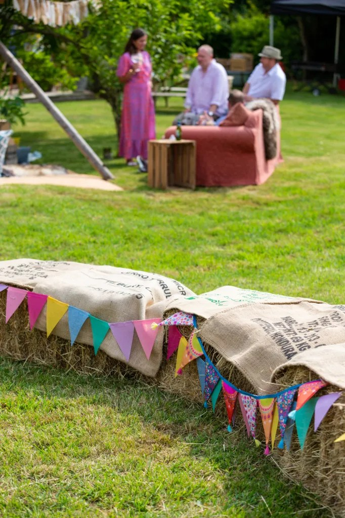 Foreground straw bales draped with coffee sacks and colourful bunting for rustic-chic party