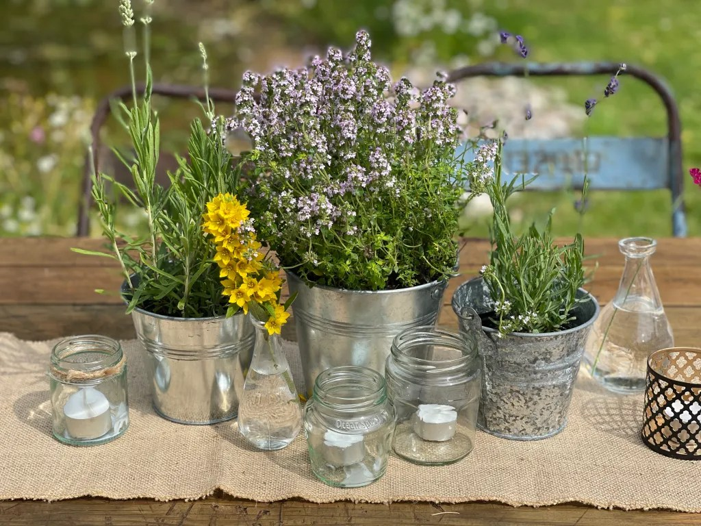 Rustic-chic table decor of herbs and flowers in galvenized metal buckets and tealights on hesian runner