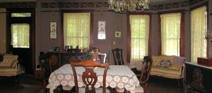 mulberry silk colored walls with an antique furnitures set and lace curtains on bay windows and side walls