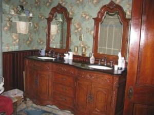 large wood ornate double sink cabinet with twin mirrors on the wall above each sink over reproduction Victorian wall paper