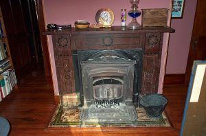 fireplace has coal insert with small rectangular victorian tiles on the hearth and mantel made of slate painted to look like dark marble