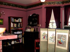 Maroon painted walls with paper trim and wood picture rail over large book cases plus curtains on windows