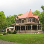 Queen Anne Victorian from southeast view - garage visible in back - large front lawn