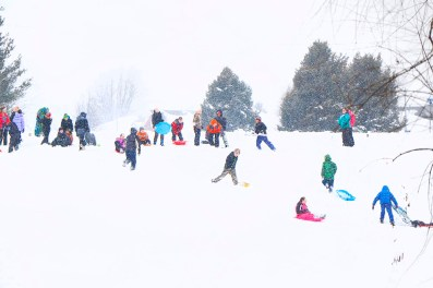 Arbor Park fifth grade students slip and slide down the slope at Arbor Park School Friday.