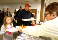 A volunteer serves up a plate of fish and fries to Sophie Weeks, her dad Jason and brother Jacob.