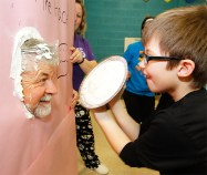 """Becket Scott pies Steve Ray . The student in each classroom that raised the most money earned a chance to """"PIE"""" a teacher. Students names were also drawn in a raffle to Pie staff members."""