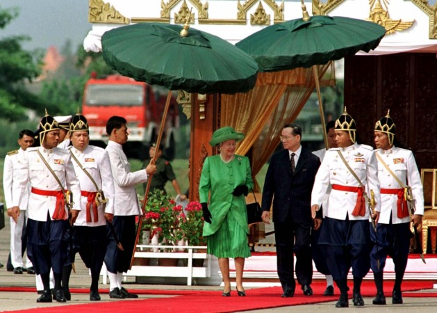 Royal guards shade Queen Elizabeth II (L) and Thai King Bhumibol Adulyadej (R) from the sun with traditional Thai parasols during the welcoming ceremony at Bangkok military airport on October 28. The Queen and The Duke of Edinburgh are in Thailand on a five-day visit to commemorate the 50th anniversary of Thai King's accession to the throne. Photo credit Reuters