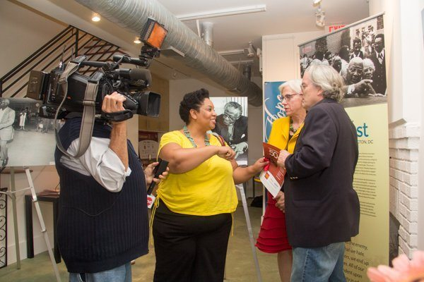Gallery On H owners, Steve and Dolly Hessler are interviewed by the Office of Cable Television during the Washington Informer's 50-50 Lens Exhibit in Northeast on Sept. 18. /Photo by Shevry Lassiter