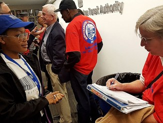 Tamia Small (left), a member of Project Retail, waits to collect a petition being signed by a member of the Amalgamated Transit Union-Local 689 at Metro headquarters in Northwest on Nov. 17. /Photo by William J. Ford