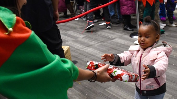 Hundreds of Ward 8 residents participate in the Cozy Christmas at Gateway toy giveaway sponsored by the Events DC and The Washington Informer Charities on Dec. 15. (Travis Riddick)
