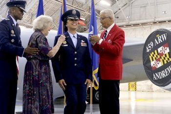 Gen. Darren W. McDew, the U.S. Transportation Command commander, watches as former Women Air Force Service Pilot Pauline Cutler-White and retired Col. Charles McGee, one of the original Tuskegee Airmen, pin new rank on Lt. Gen. Stayce D. Harris. (U.S. Air Force photo/Andy Morataya)