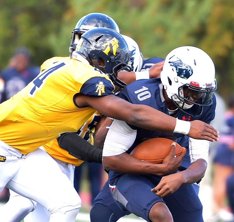 Howard Bison quarterback Jason Collins is tackled by North Carolina A&T defenders as he runs for a first down during the Aggies' 34-7 win in what was Howard's homecoming game on Saturday, Oct. 22 at William H. Greene Stadium in northwest D.C. /Photo by John E. De Freitas
