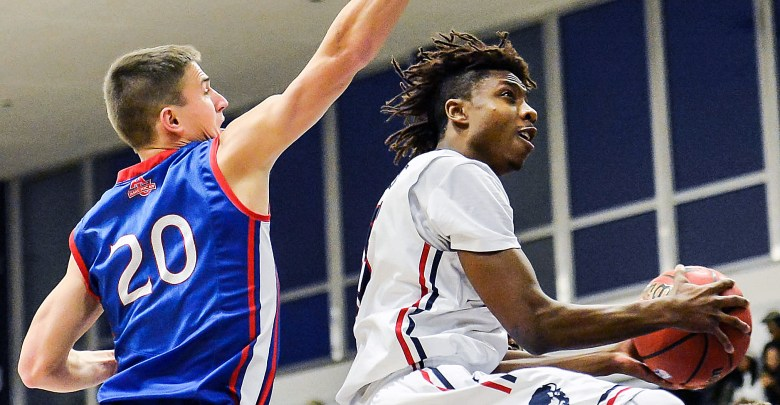 Howard Bison guard Damon Collins sails past American University Eagles guard Charlie Jones in the first half of Howard's 71-54 win at Burr Gymnasium in Northwest on Saturday, Dec. 3. /Photo of courtesy Abdullah Yusuf